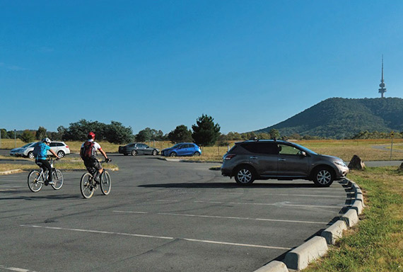 People leaving carpark on bikes with Telstra Tower in the background